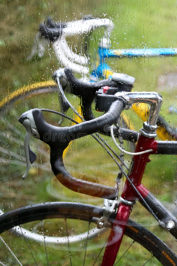 Bicycles in the rain. Two parked bicycles are parked side by side outside of a glass window, which shows the rain drops stock photography