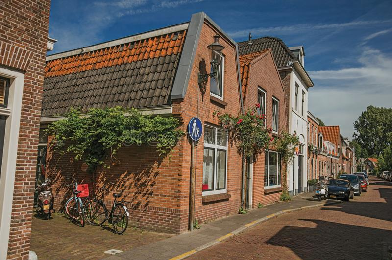 Bicycles and scooter in front of brick house in a narrow street corner under sunny blue sky at Weesp. royalty free stock image