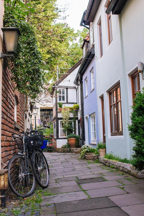 Bicycles and trees in cozy backyard. Summer patio with bikes. Bicycles in front of old house. Traditional exterior in Europe. stock photography