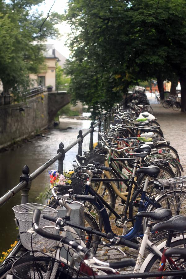 Bicycles over the canal of Uppsala. Bicycles in the rain, over the canal of Uppsala. Bikes. Wet saddles stock image