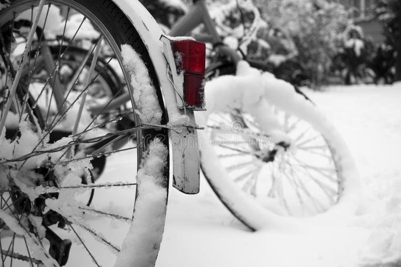 Bicycles wheels in a snow in a bicycle parking. Magic winter weather covered bicycles wheels by snow and ice. Distinct red coloured bicycle`s headlight looks stock photos