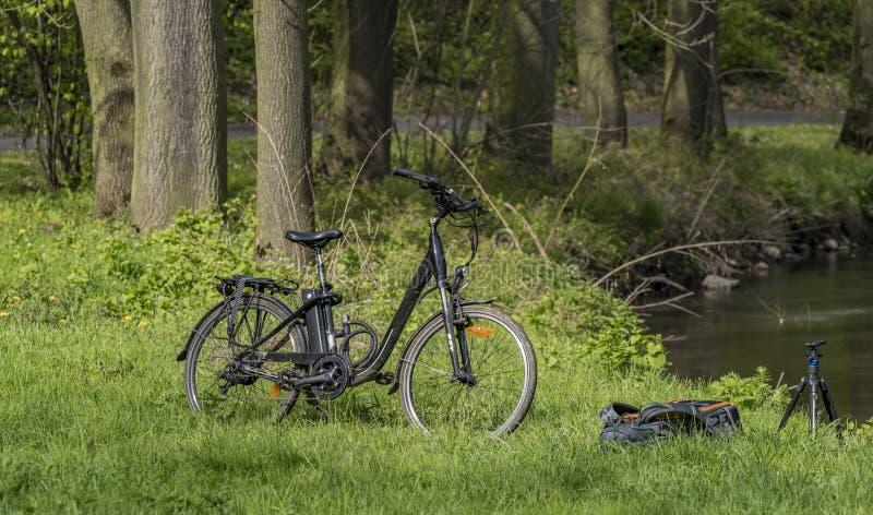 Bicyclette électrique avec le sac à dos et le trépied dans l'herbe photographie stock libre de droits
