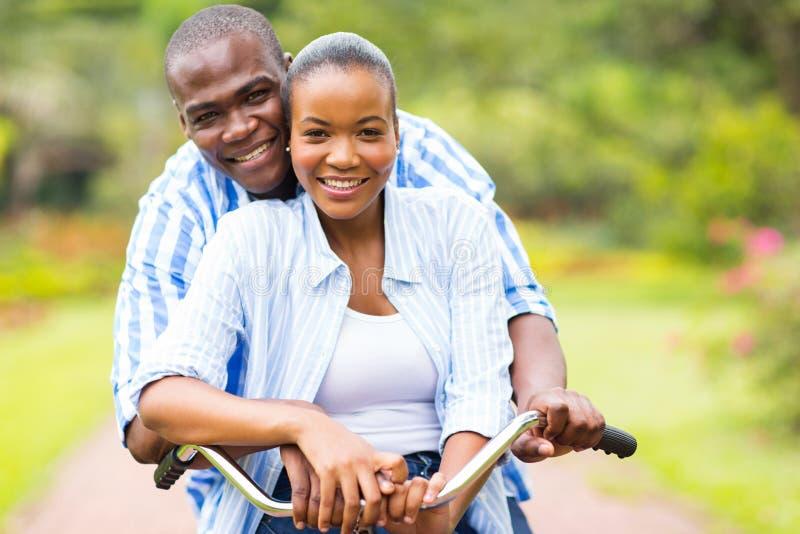 Bicyclette africaine d'équitation de couples photographie stock