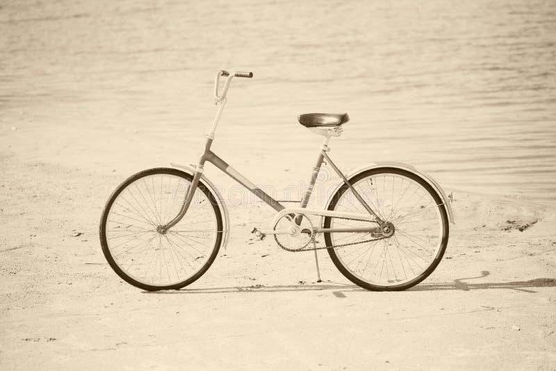 Bicyclette antique sur la plage - rétro sépia images stock