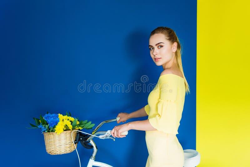 Bicyclette attrayante de participation de jeune fille avec des fleurs dans le panier sur le bleu photo stock