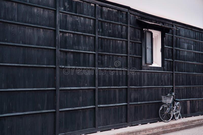 Bicyclette blanche de vintage japonais avec le mur en bois noir du vieux hou image stock