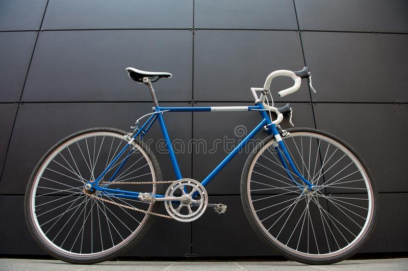 Bicyclette bleue de ville de vintage sur un mur noir images stock