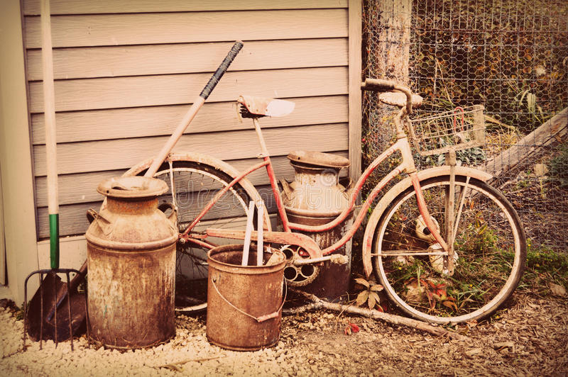Bicyclette, cruche de lait et outils antiques photo stock