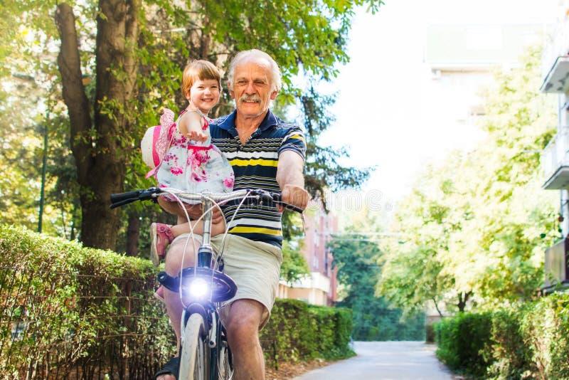 Bicyclette d'équitation d'homme supérieur avec la petite-fille photo stock