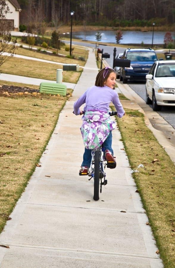 Bicyclette d'équitation de fille dans le voisinage photo stock