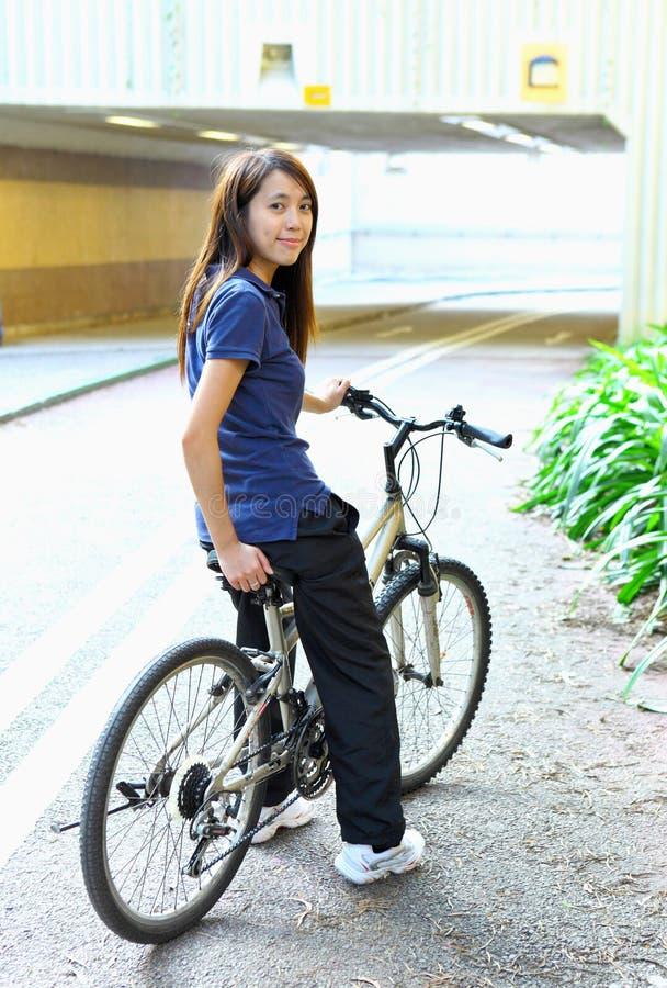 Bicyclette d'équitation de jeune femme photo stock