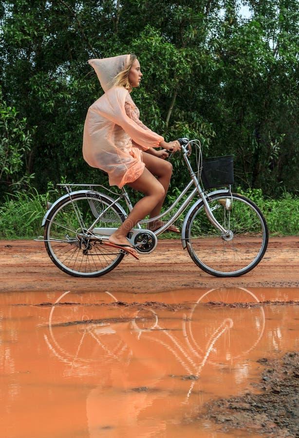 Bicyclette d'équitation de jeune femme sous la pluie tropicale d'été images libres de droits
