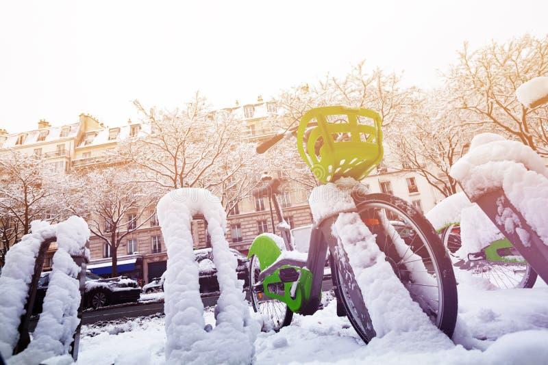 Bicyclette de Paris se garant au jour d'hiver neigeux photo stock