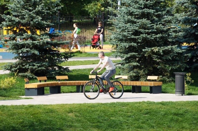 Bicyclette de tour d'homme en parc de Butovo, Moscou, Russie image stock