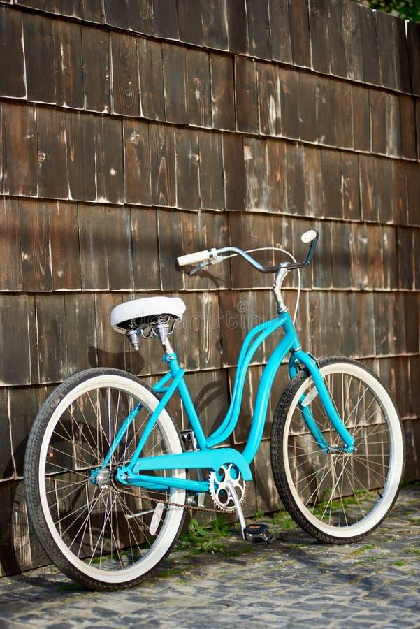 Bicyclette de turquoise près du mur en bois photographie stock