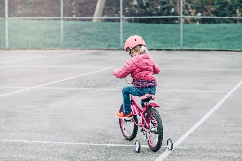 Bicyclette de v?lo de rose d'?quitation de fille d'?l?ve du cours pr?paratoire dans le casque sur la route d'arri?re-cour dehors  images libres de droits