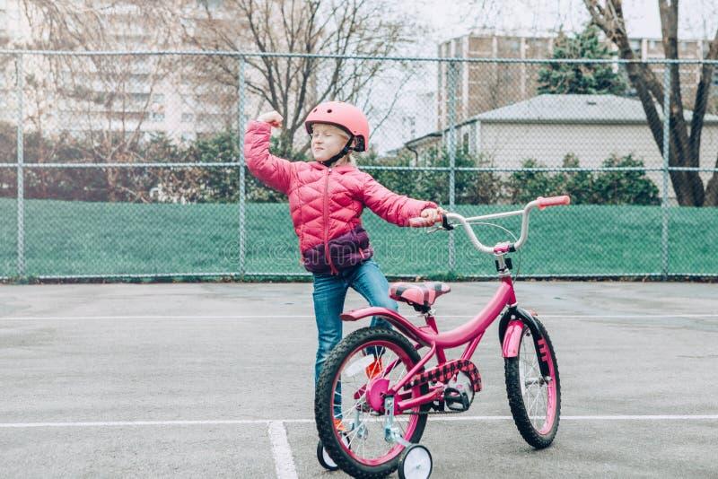 Bicyclette de v?lo de rose d'?quitation de fille d'?l?ve du cours pr?paratoire dans le casque sur la route d'arri?re-cour dehors  images stock