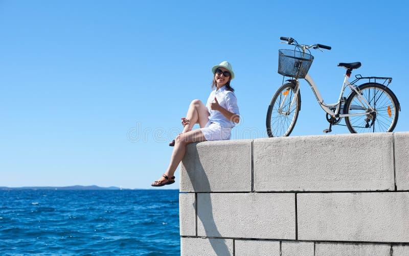 Bicyclette de ville d'?quitation de jeune femme pr?s de mer image libre de droits