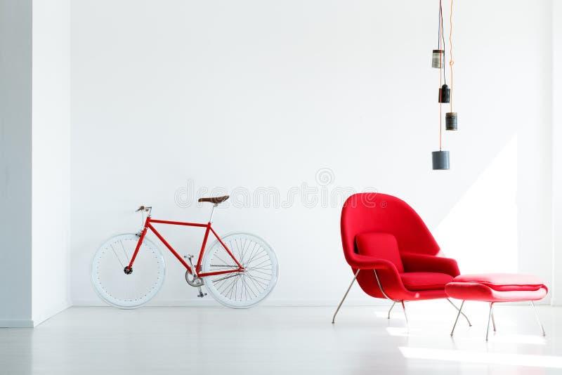 Bicyclette et fauteuil rouges sous la lampe en appartement minimal blanc i image stock