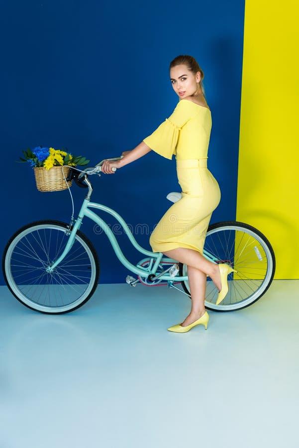 Bicyclette femelle de participation de mannequin sur le bleu photos stock