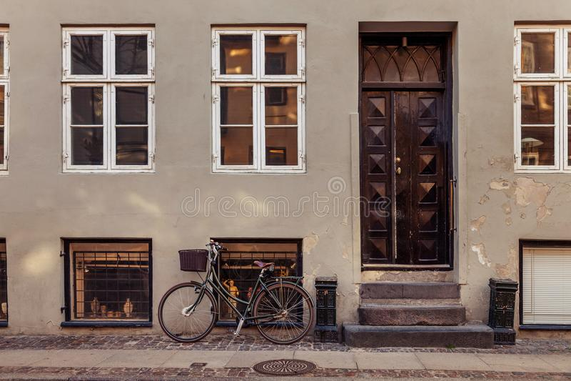 bicyclette garée avec le panier près du bâtiment gris avec les portes fermées sur la rue images libres de droits