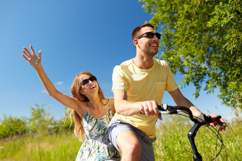 Bicyclette heureuse d'équitation de couples ensemble en été photographie stock libre de droits