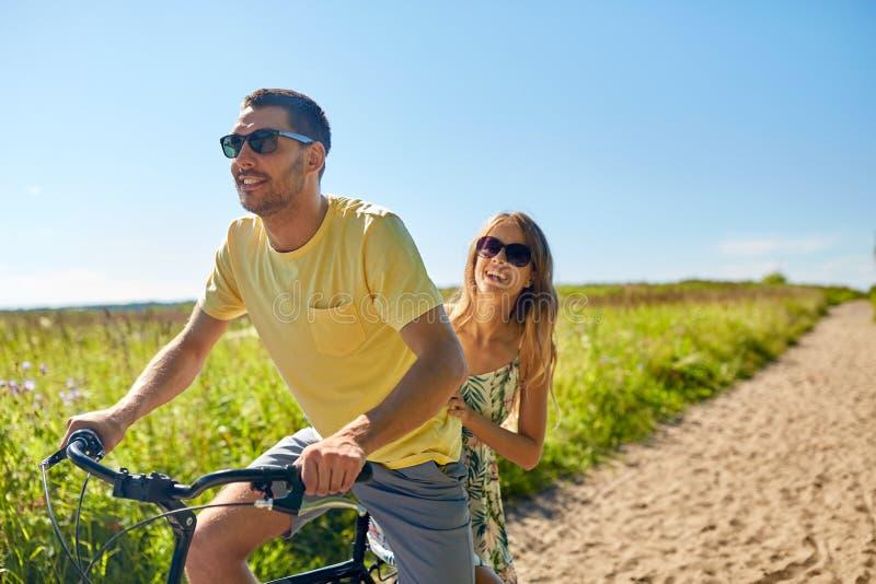 Bicyclette heureuse d'équitation de couples ensemble en été photos stock