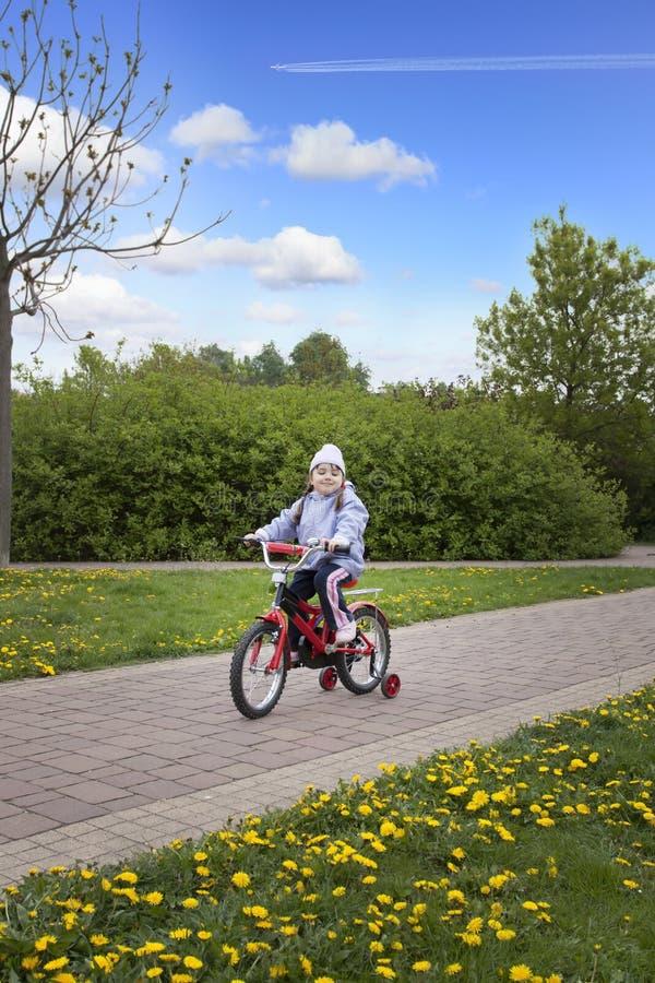 Bicyclette heureuse d'équitation de fille de pround images stock