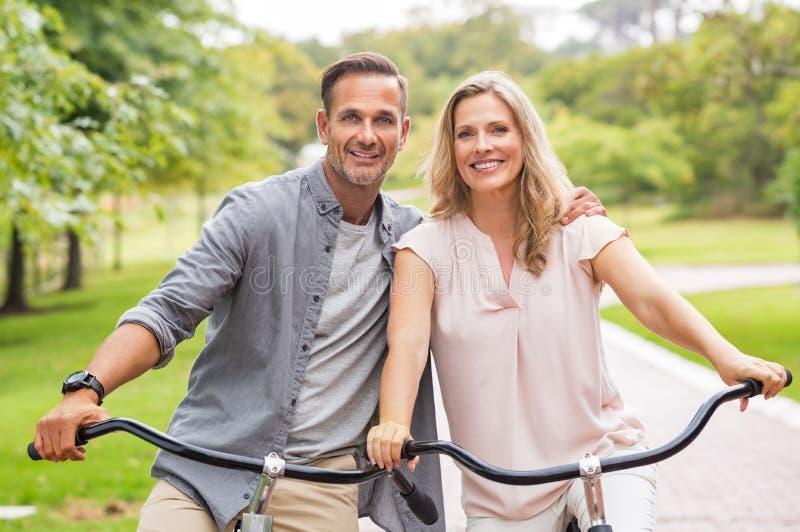 Bicyclette mûre d'équitation de couples photo stock