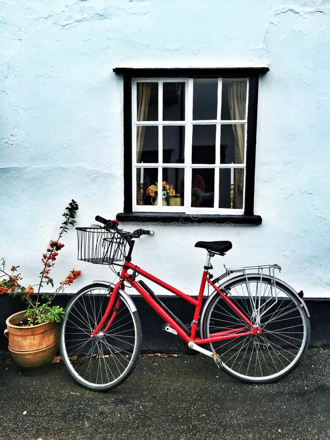 Bicyclette rouge sous une fenêtre images libres de droits