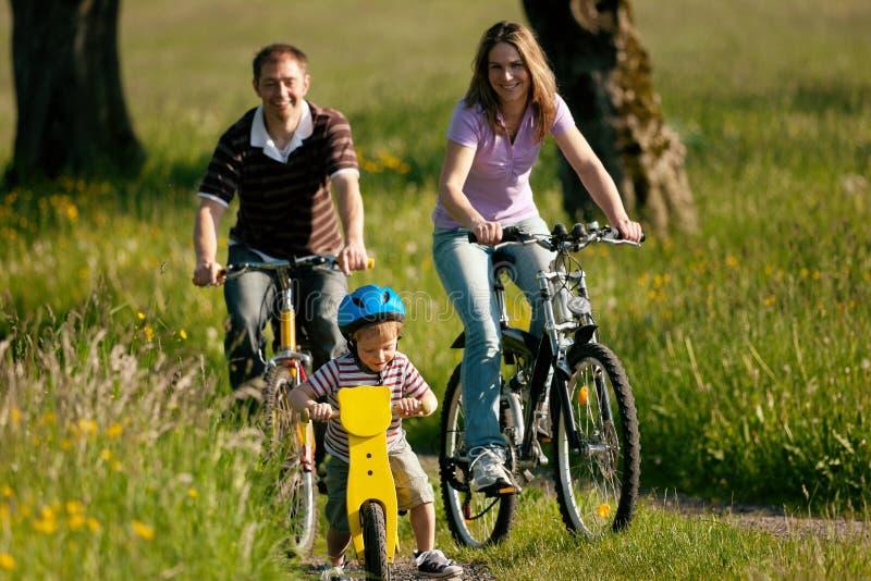 Bicyclettes d'équitation de famille en été photo stock
