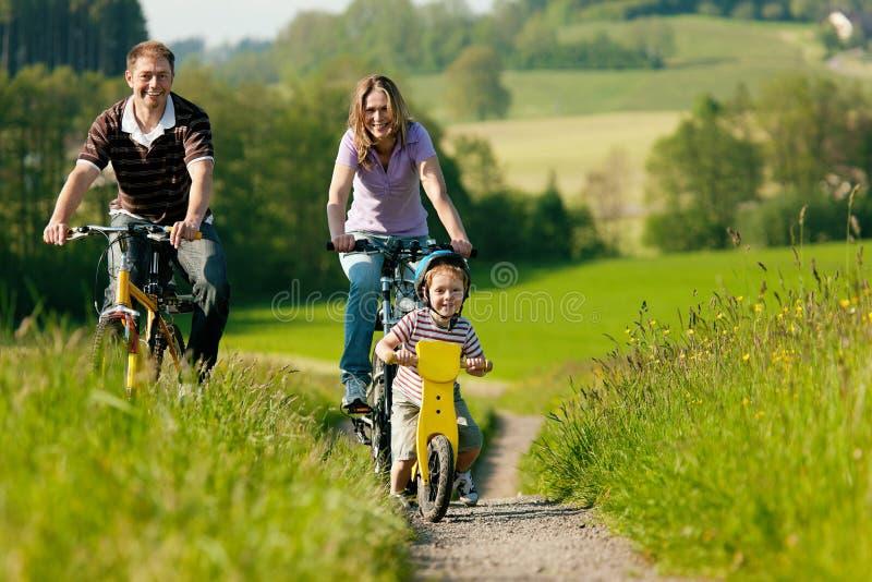Bicyclettes d'équitation de famille en été photographie stock