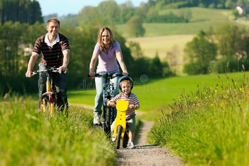 Bicyclettes d'équitation de famille en été images stock