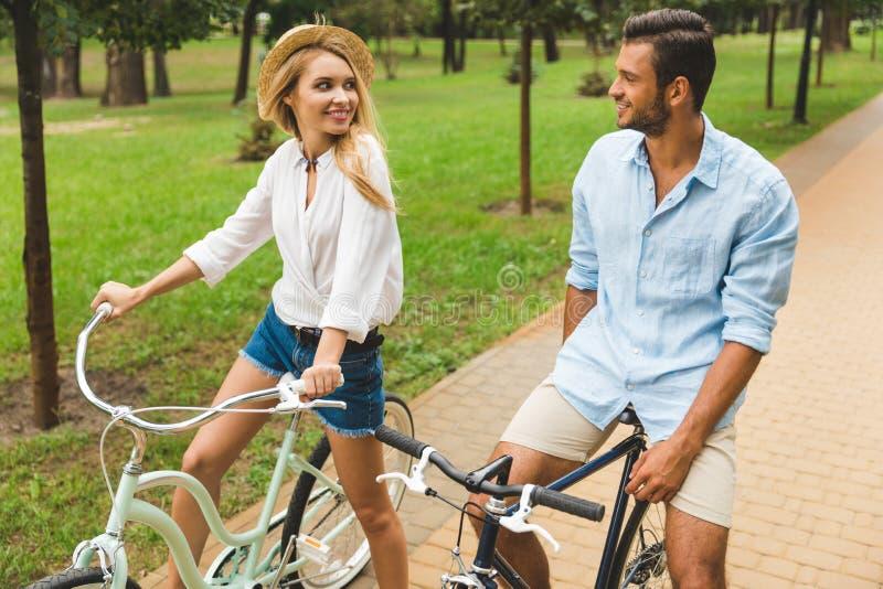 bicyclettes de monte de jeunes couples heureux ensemble photo libre de droits