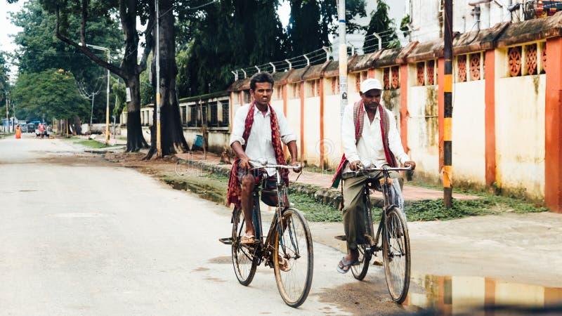 Bicyclettes de monte de personnes indiennes sur la rue tout en pleuvant chez Bodh Gaya, le Bihar, Inde photos stock