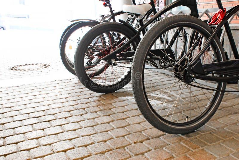 Bicyclettes gar?es sur le trottoir Stationnement de bicyclette de v?lo sur la rue photo stock