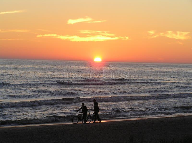 Bicyclettes sur la plage de coucher du soleil image libre de droits
