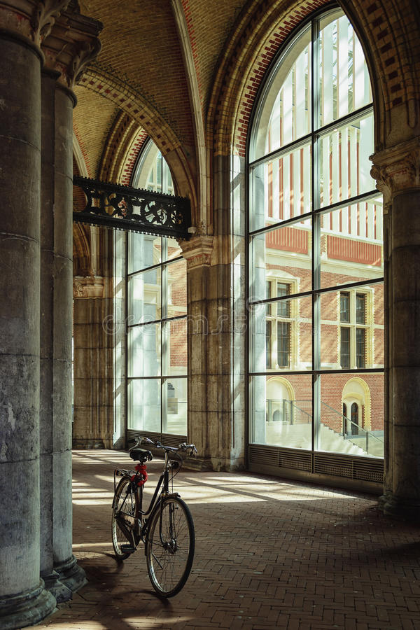 Bicycling around the column. Corridor in a museum building with large windows and a bicycle parked near the column royalty free stock photography