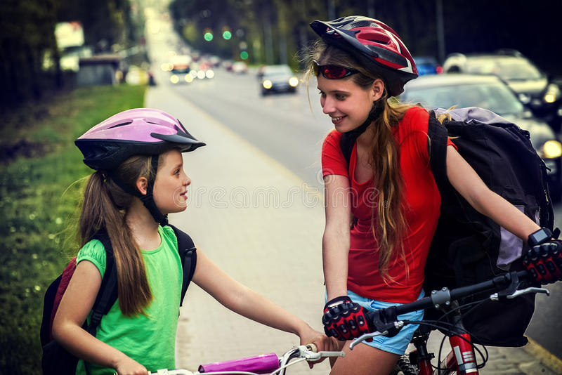 Bicyclist child ride on city bicycle path . Girls wearing helmet . Bicyclist child ride on bicycle path in city. Girls wearing helmet with rucksack . Cyclists stock photo