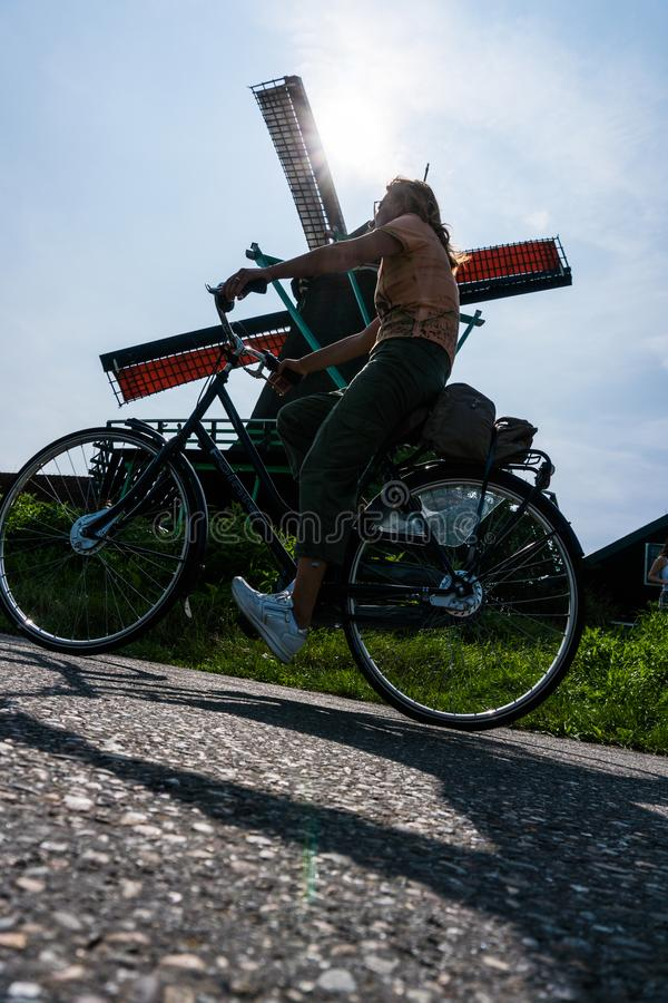 Bicyclist girl riding in front of Zaanse Schans green Windmill stock photo