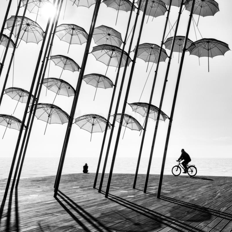 A bicyclist and a girl under the umbrellas royalty free stock photography