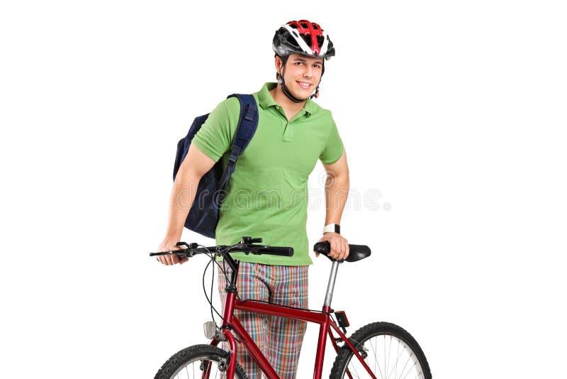 Bicyclist joven que presenta al lado de una bicicleta imágenes de archivo libres de regalías