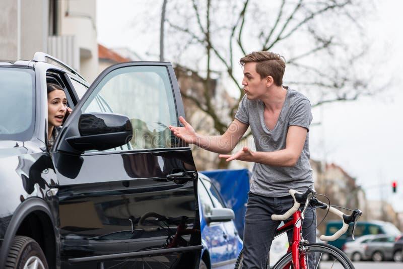 Bicyclist krzyczy podczas gdy swerving dla unikać karambol na ruchliwej ulicie obraz royalty free