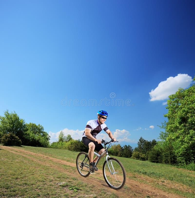 Bicyclist masculino que monta una bici de montaña cuesta abajo imagen de archivo
