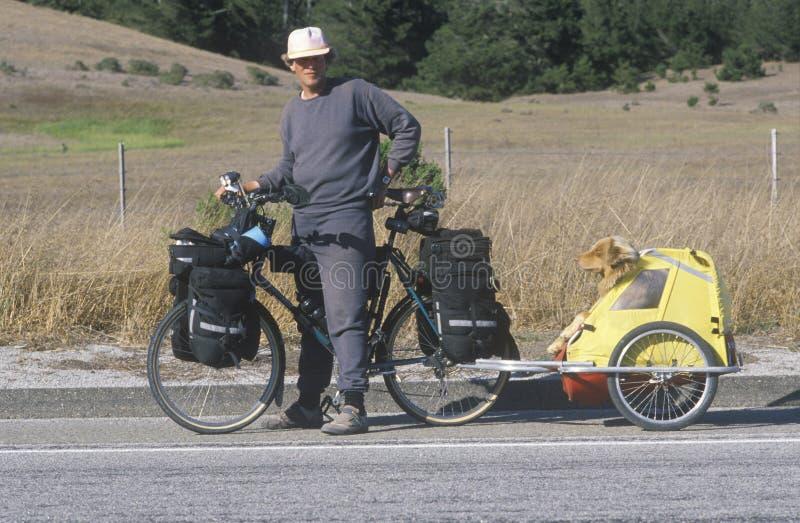 Bicyclist masculino que presenta con el perro en portador imagenes de archivo