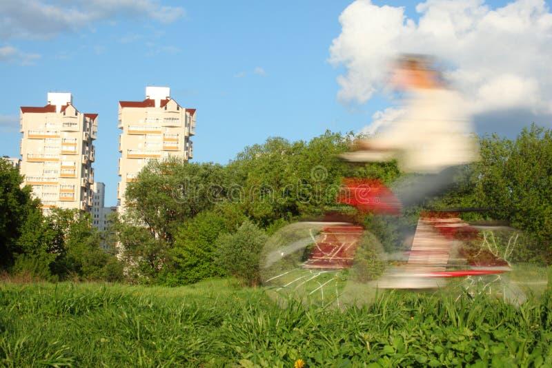 Bicyclist no borrão de movimento de encontro às árvores e às casas foto de stock royalty free