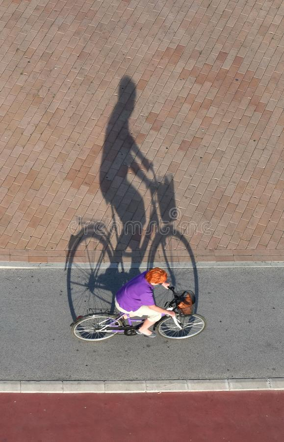 Bicyclist riding bicycle top view with shadow stock photography