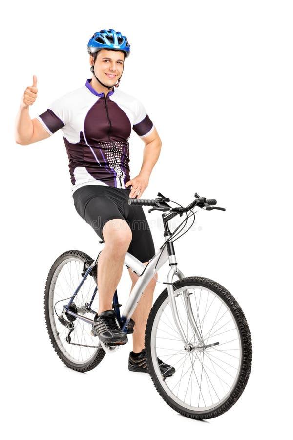 Bicyclist sonriente que presenta y que da un pulgar para arriba imagen de archivo libre de regalías