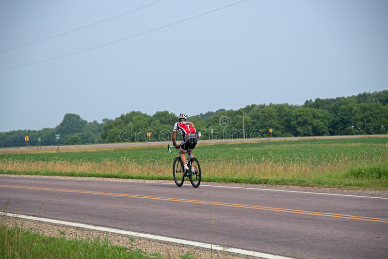 A Bicyclist Traveling on a Country Road. Cycling, also called bicycling or biking, is the use of bicycles for transport, recreation, exercise or sport. Persons royalty free stock photo