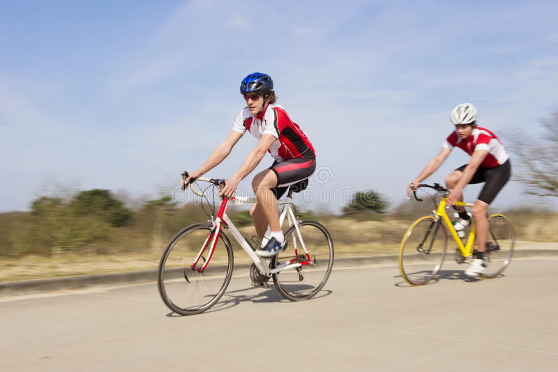 Bicyclists Riding On An Open Country Road. Active male athletes riding bicycles on an open country road royalty free stock photography